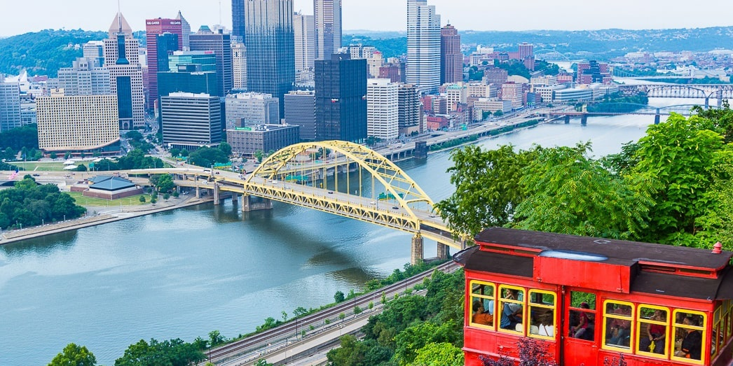 Photo of Pittsburgh's red incline car framing the city's skyline in the distance.