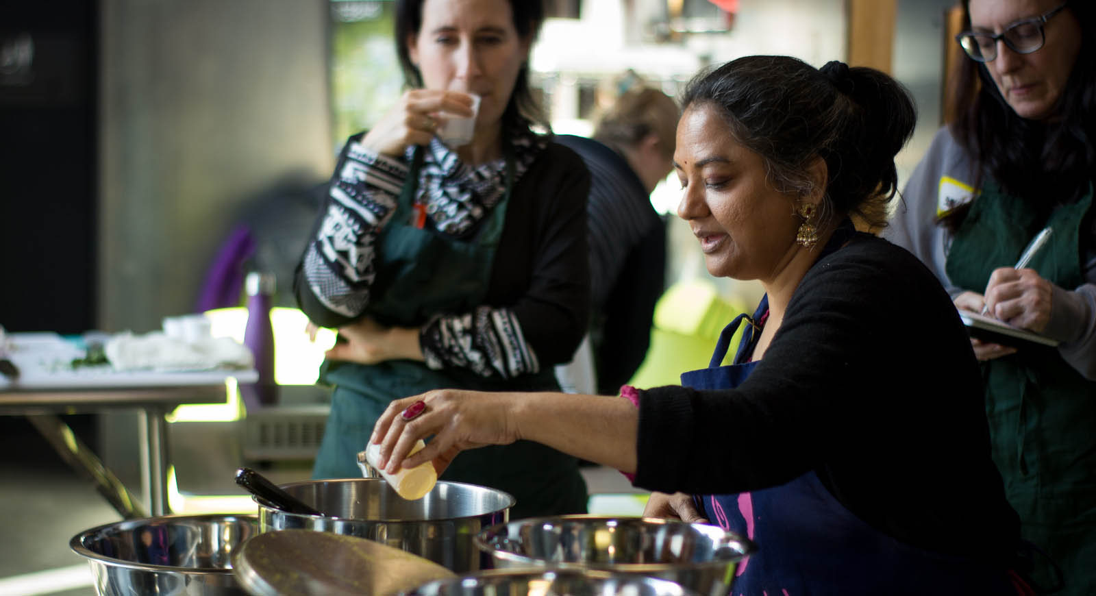 Photo of an Indian woman leading a cooking class, while two women in the background pay attention.
