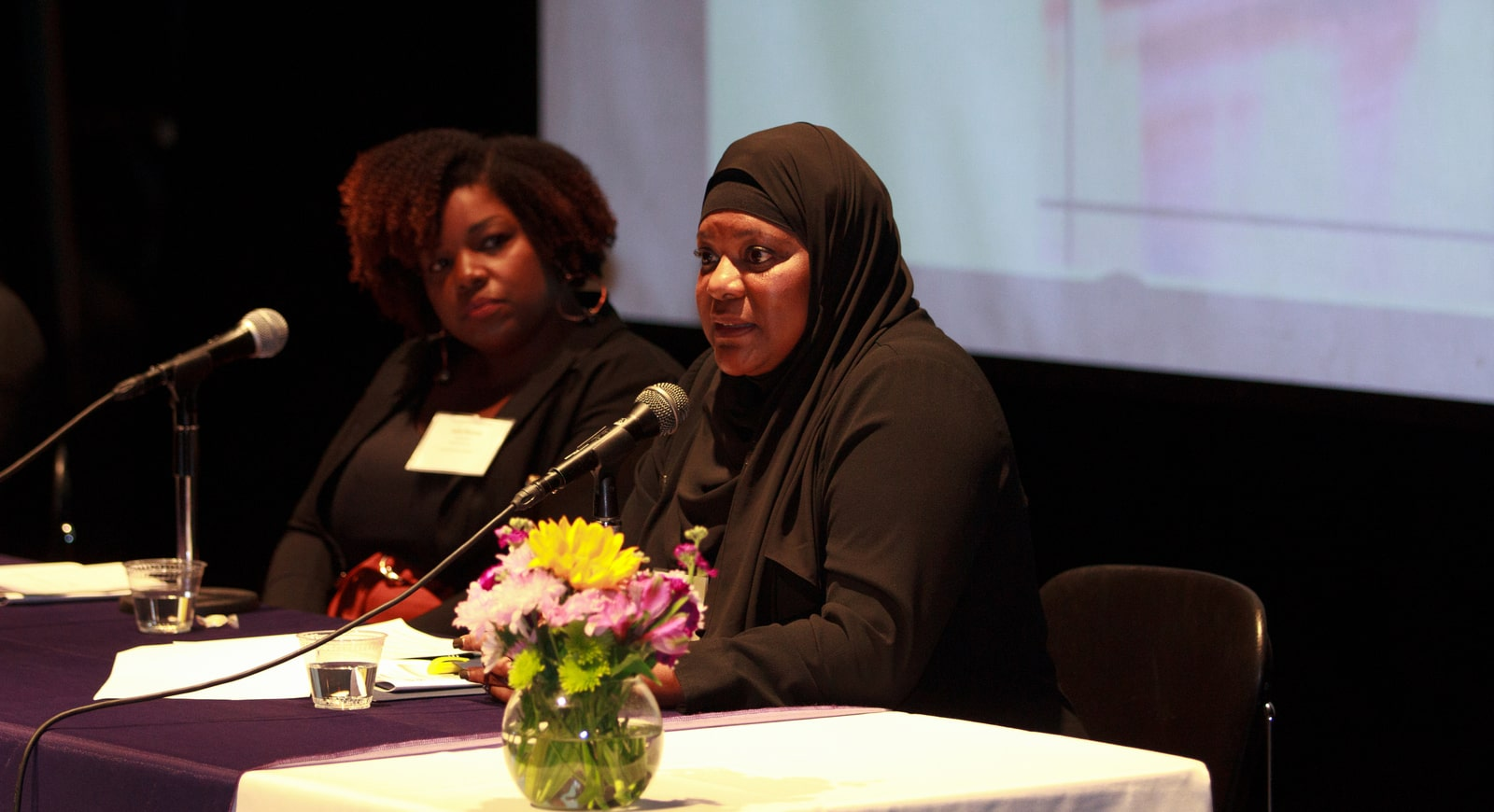 Photo of two Black women on a panel. The hijabi woman is speaking, while the woman beside her listens.