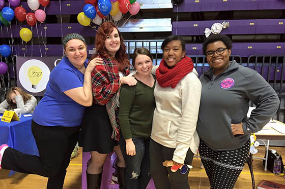 Photo of a group of Chatham students posing at an event, with balloons in the background