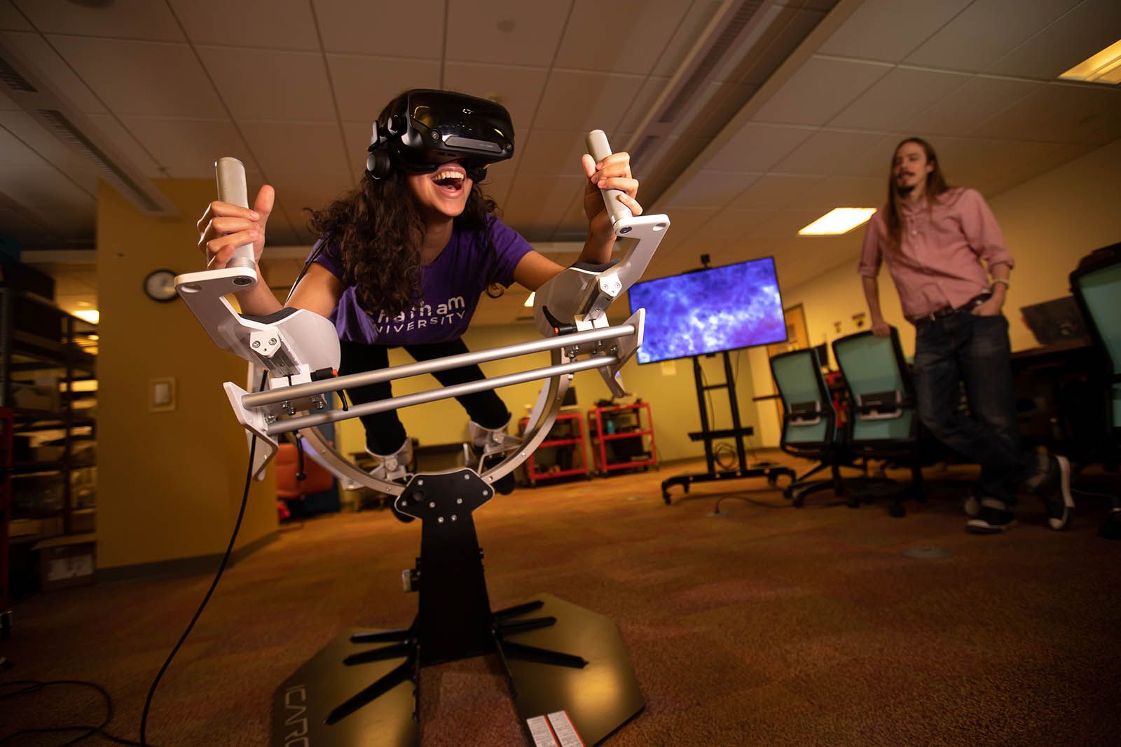 Photo of a Chatham University Immersive Media student in a virtual reality machine, smiling, while a professor sits near.